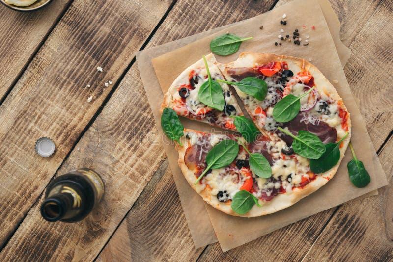在木桌上的意大利自创薄饼用低度黄啤酒 免版税库存图片