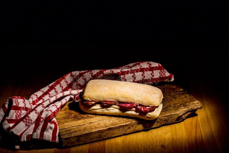 在木桌上的意大利蒜味咸腊肠三明治 免版税图库摄影