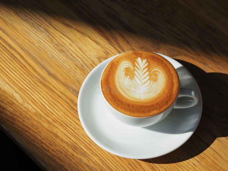 在木桌上的拿铁或热奶咖啡艺术咖啡杯顶视图与在咖啡馆的阳光 免版税库存照片