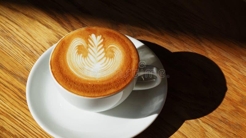 在木桌上的拿铁或热奶咖啡艺术咖啡杯顶视图与在咖啡馆的阳光 库存照片
