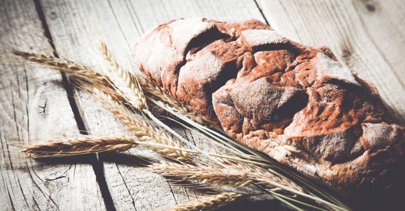 在木桌上的新近地被烘烤的传统面包 图库摄影