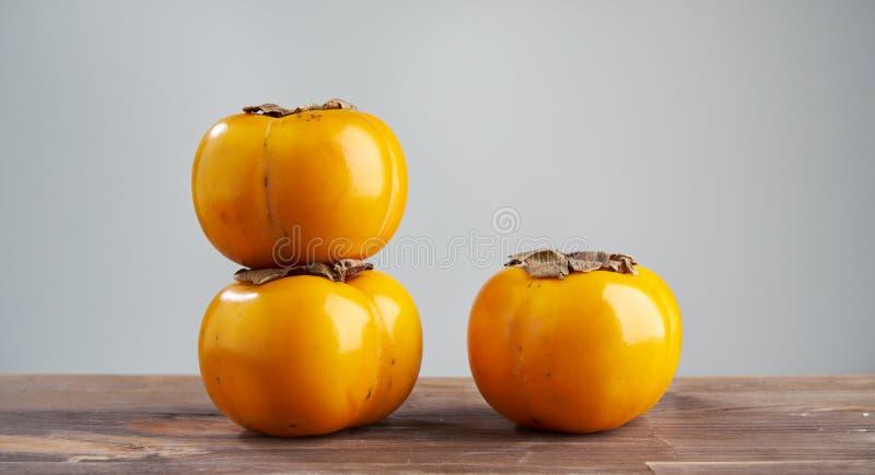 在木桌上的新鲜水果柿子 创造性的概念的健康吃食物和营养,布局的空间 库存照片