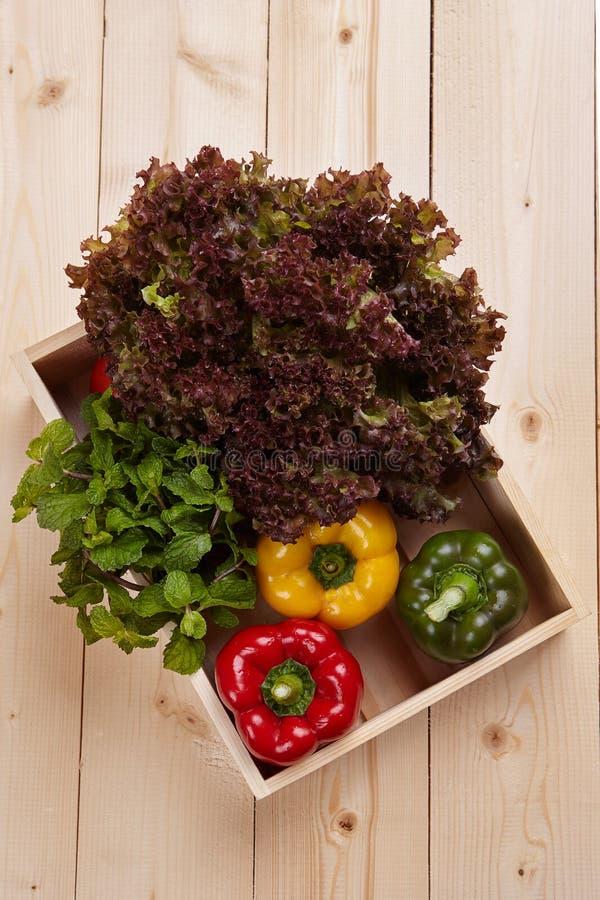 在木桌上的新鲜的五颜六色的甜椒箱子 免版税库存照片