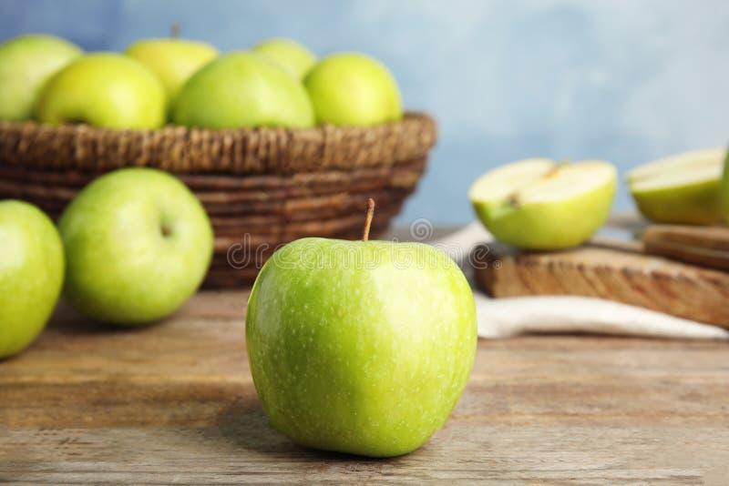 在木桌上的新鲜的成熟绿色苹果反对蓝色背景 免版税图库摄影