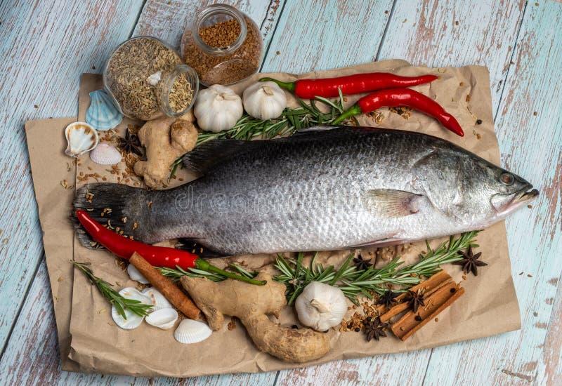 在木桌上的新鲜的未加工的鲈鱼由新鲜的成份和香料围拢了 免版税图库摄影