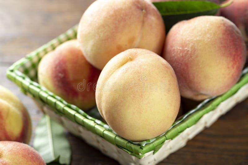 在木桌上的新鲜的甜桃子 库存照片