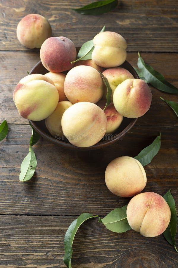在木桌上的新鲜的甜桃子 免版税库存图片