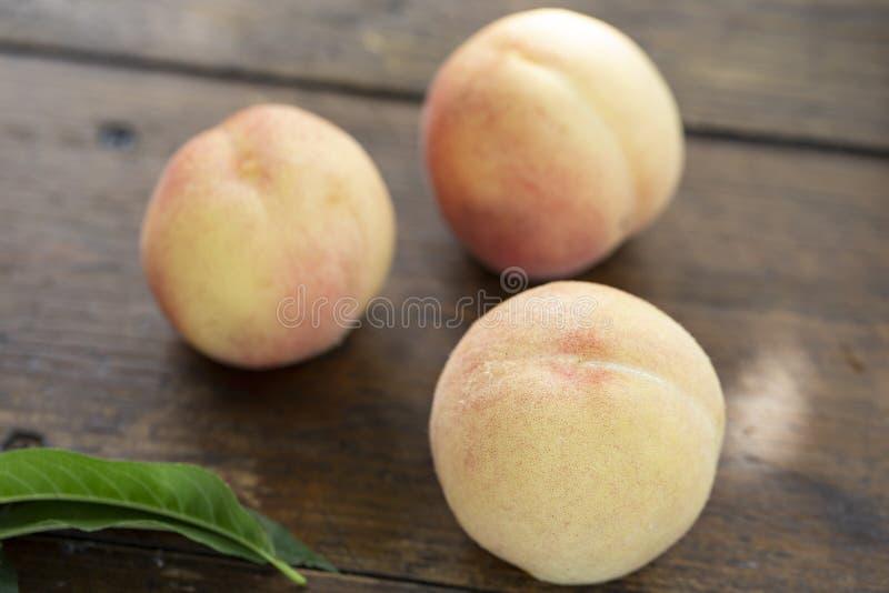 在木桌上的新鲜的甜桃子 免版税库存照片