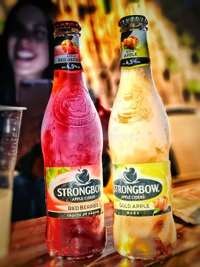 在木桌上的新鲜的Strongbow瓶 红色莓果和金苹果 愉快的女孩在背景中 免版税库存照片
