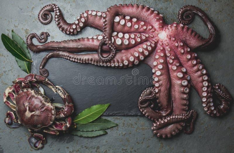 在木桌上的未加工的新鲜的章鱼与月桂树 顶视图 免版税库存照片