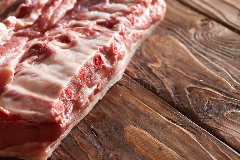 在木桌上的未加工的猪肉 在骨头或烘烤的简单派唯一的肉胸肉从哪个油炸物烽火台 免版税图库摄影