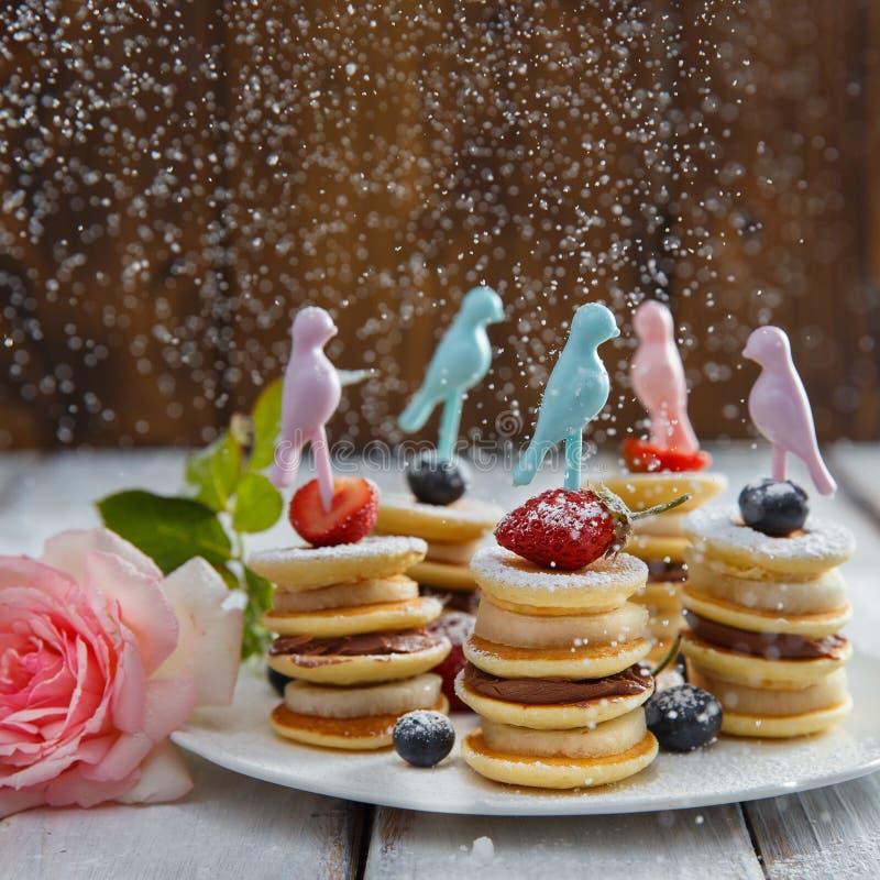 在白色木桌上的果子、莓果和薄煎饼点心 免版税图库摄影