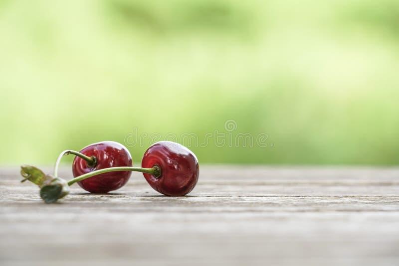 在木桌上的樱桃果子在bokeh绿色背景 免版税库存图片