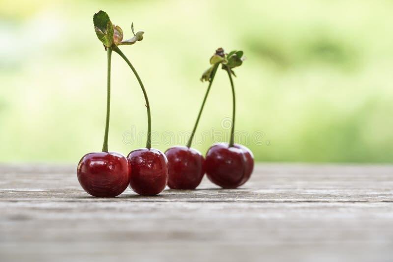 在木桌上的樱桃果子在bokeh绿色背景 库存照片