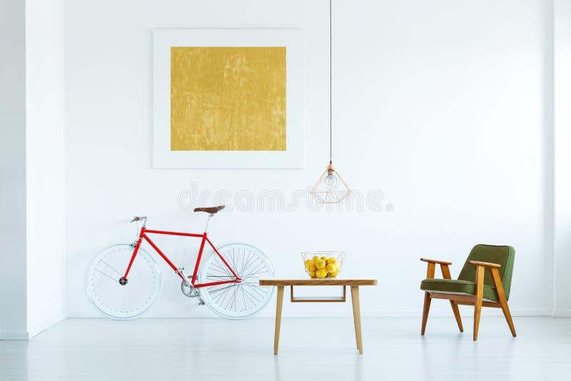 在木桌上的灯在与绿色armcha的白色平的内部 免版税库存照片