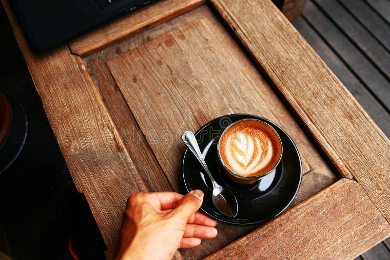 在木桌上的热的咖啡拿铁与右手服务 库存照片