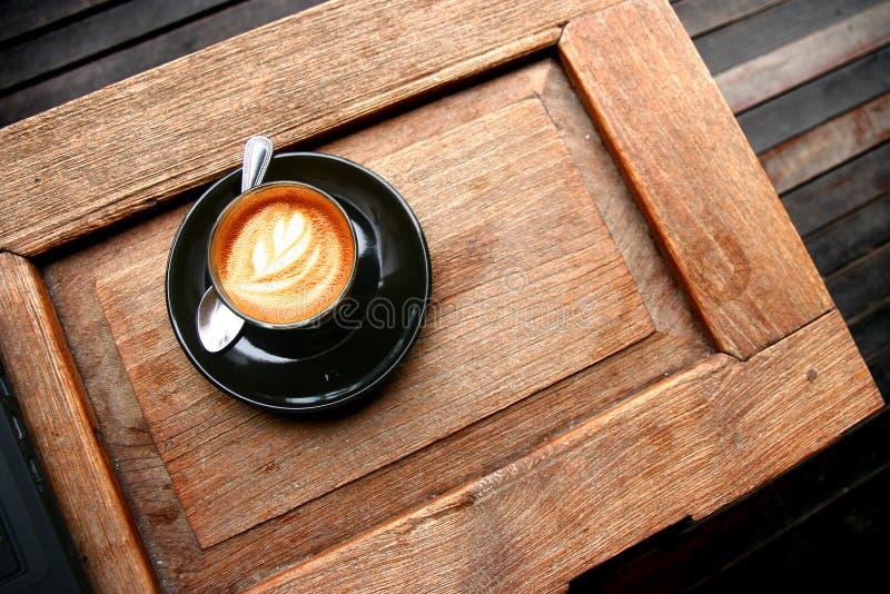 在木桌上的热的咖啡拿铁 库存图片