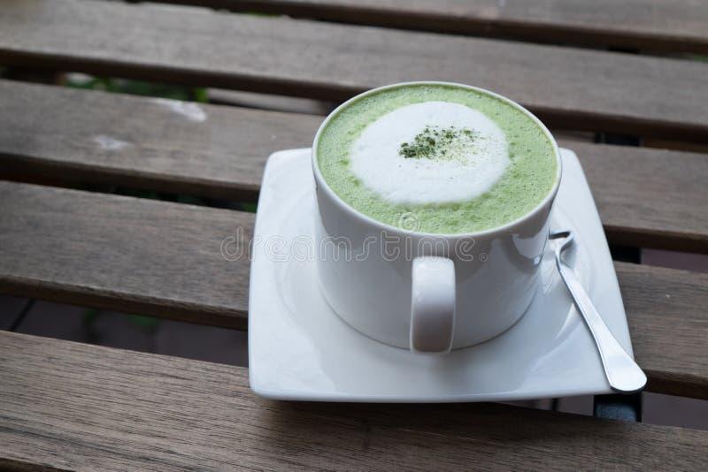 在木桌上的热的绿茶 库存图片