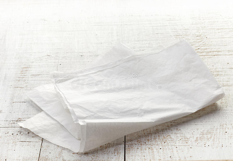 在木桌上的白色包装纸 免版税库存图片