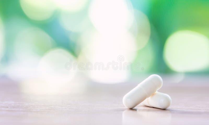 在木桌上的白色医学胶囊有自然本底 库存图片