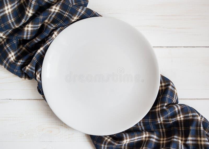 在木桌上的白色空的板材与方格的餐巾 免版税库存照片