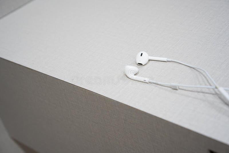 在木桌上的白色耳机 免版税库存图片