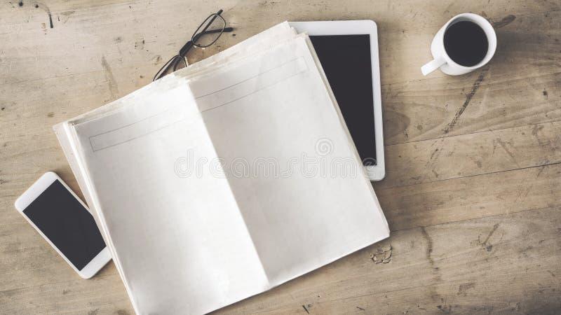 在木桌上的空的报纸手机片剂咖啡杯玻璃 图库摄影