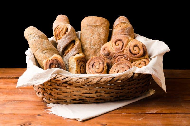 在木桌上的篮子上添面包有黑背景 免版税库存照片