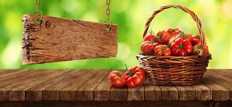 在木桌上的篮子里新鲜的番茄 免版税库存图片
