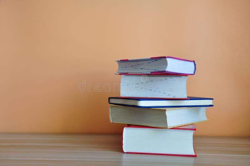 在木桌上的精装书书有黄色背景 库存照片