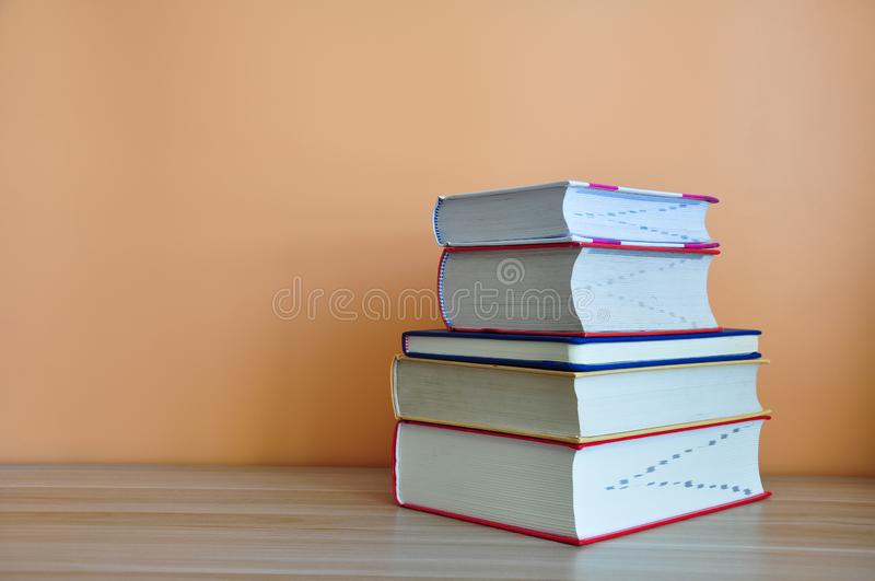 在木桌上的精装书书有黄色背景 库存图片