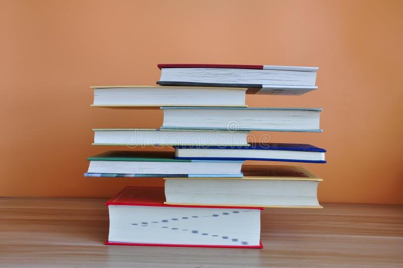 在木桌上的精装书书有黄色背景 免版税库存照片