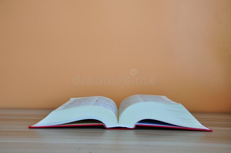 在木桌上的精装书书有黄色背景 免版税图库摄影