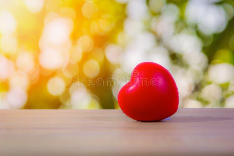 在木桌上的红色心脏与bokeh光 免版税库存图片