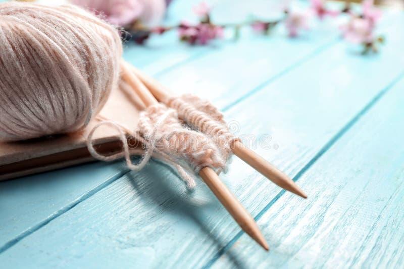 在木桌上的编物纱和书球与针的 免版税库存图片