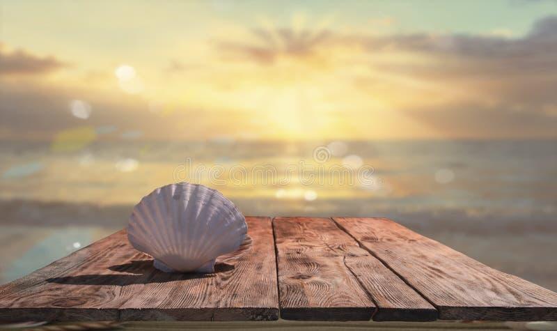 在木桌上的美丽的贝壳反对蓝色海和海日落 库存照片