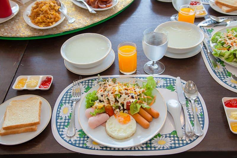 在木桌上的美国早餐 美国早餐用鸡蛋、香肠、面包和菜, 免版税库存图片