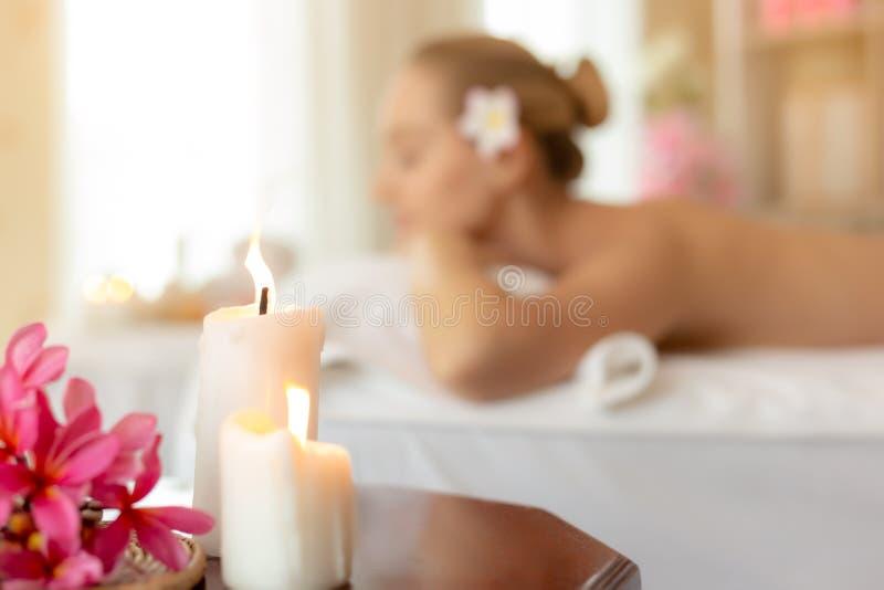 在木桌上的美好的蜡烛在有美女的温泉屋子里温泉沙龙背景的 迷人的美丽的顾客说谎有倾向  库存图片