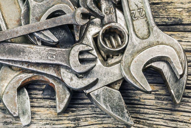 在木桌上的老生锈的金属扳手 库存照片