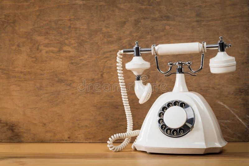 在木桌上的老白色电话有颜色墙壁背景 库存图片
