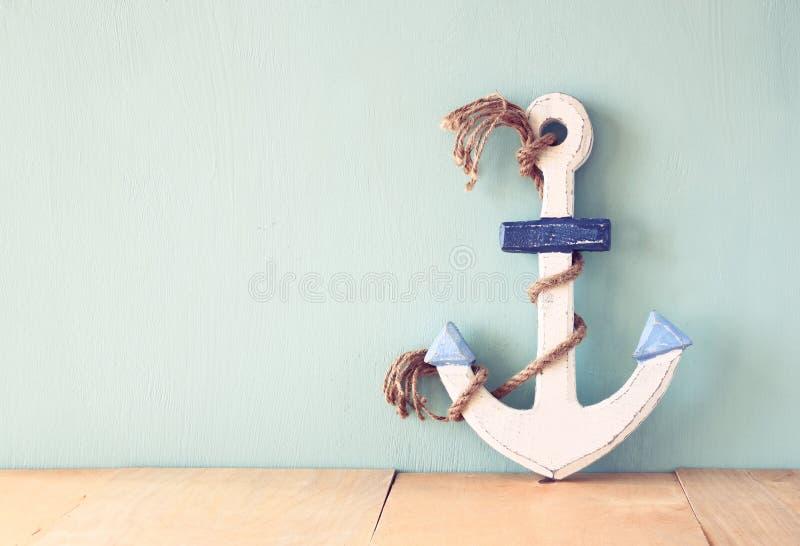 在木桌上的老船舶船锚在木水色背景 图库摄影