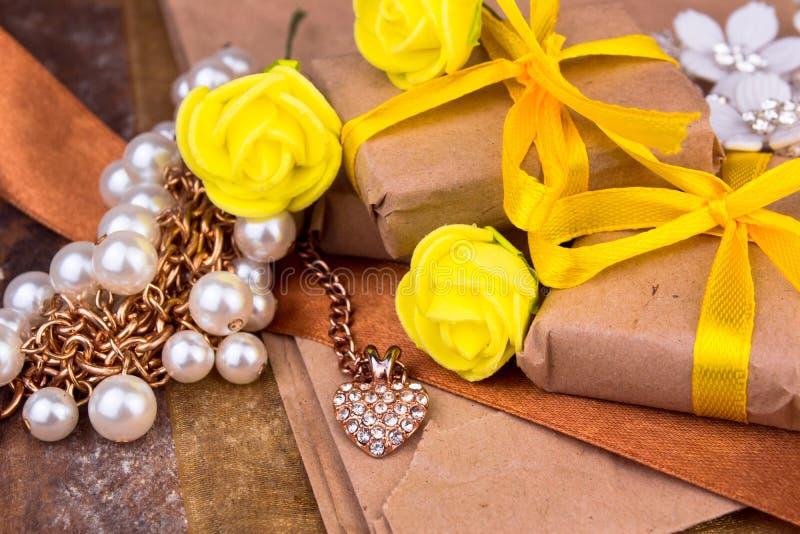 在木桌上的自然纸包裹的黄色礼物盒 免版税库存照片