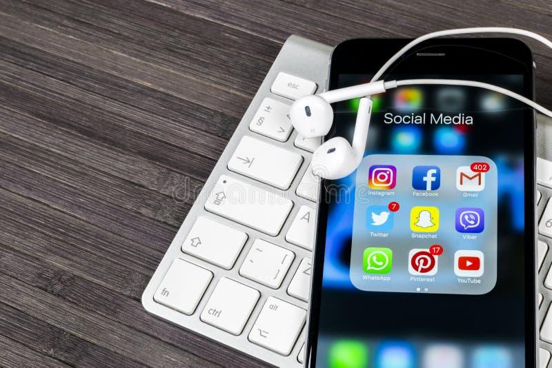 在木桌上的苹果计算机iPhone 7与社会媒介facebook, instagram,慌张,在屏幕上的snapchat应用象  智能手机 库存照片