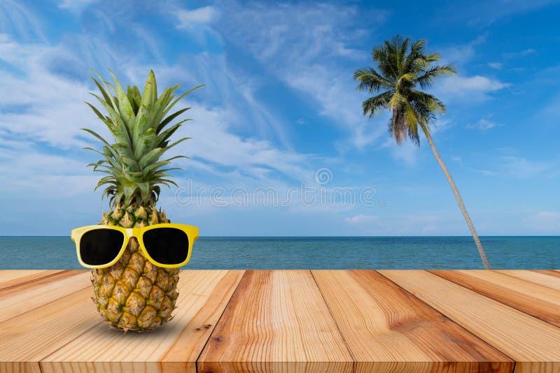 在木桌上的菠萝在一个热带风景,时尚行家菠萝,明亮的夏天颜色,与太阳镜的热带水果 免版税图库摄影