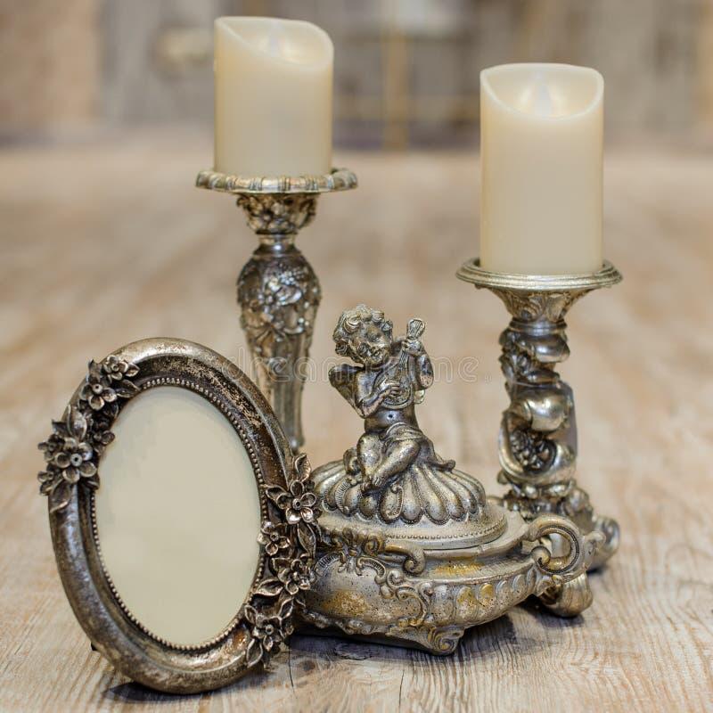 在木桌上的葡萄酒古董古典框架的图象和蜡烛 免版税库存照片