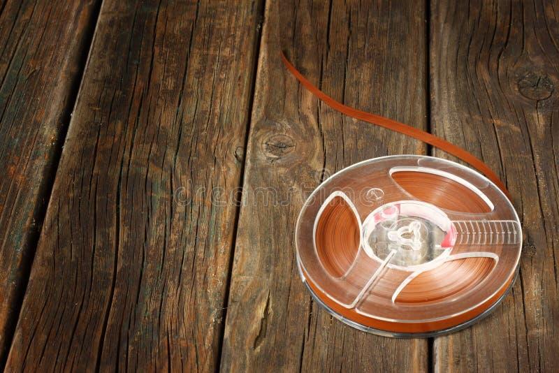 在木桌上的葡萄酒磁性音频卷轴。音乐概念背景。 免版税库存图片