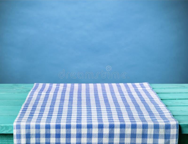 在木桌上的蓝色方格的餐巾 免版税库存图片