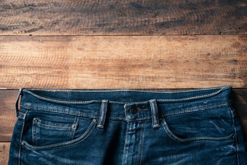 在木桌上的蓝色牛仔布牛仔裤 免版税库存图片