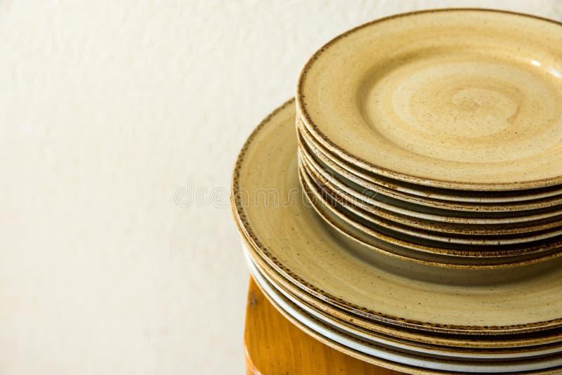 在木桌上的被堆积的棕色有斑点的给上釉的陶器陶瓷板材盘 白色墙壁背景 地中海的厨房 图库摄影