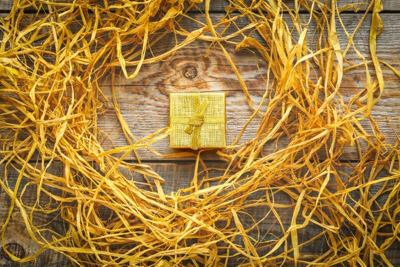 在木桌上的金黄礼物盒与酒椰或麻线 库存图片